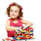 Den lilla flickan bygger ett hus från plast- kvarter royaltyfri fotografi