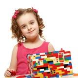 Den lilla flickan bygger ett hus från plast- kvarter royaltyfria foton
