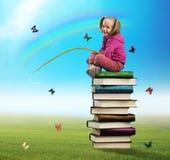 Den lilla flickan sitter på högen av böcker Royaltyfri Bild
