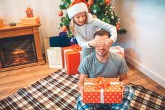 Den lilla flickan står bak hennes fader och håller hans ögon closeed med händer Han rymmer den röda asken med gåva Den unga manne arkivbilder