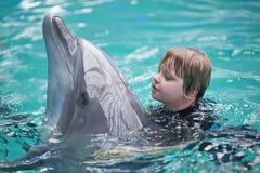 Den lilla flickasimningen i pölen med en delfin Arkivbild