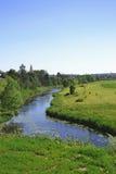 Den lilla floden som igenom kör nära kyrkan Arkivbild