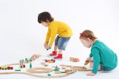 Den lilla fokuserade pojken och flickan bygger järnvägen från trädelar royaltyfria foton