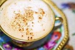 Den lilla från gångna tider blommiga porslinkoppen med kaffe och mjölkar mousse som strilas med kanel Royaltyfria Bilder