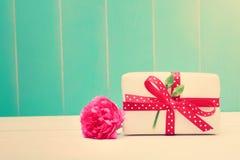 Den lilla gåvaasken med nejlikor på kricka färgade trä Royaltyfria Bilder