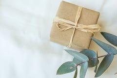 Den lilla gåvaasken som slås in i brunt hantverkpapper som binds med, tvinnar silverdollareukalyptusfilialen på den vita linnetyg Royaltyfri Fotografi