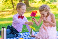 Den lilla gentlemannen ger flickan per grupp av blommor fotografering för bildbyråer