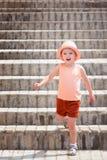 Den lilla glade flickan gick ner trappan Ett barn som bär en stilfull hatt och röda kortslutningar royaltyfri bild