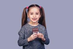 Den lilla glade flickan rymmer choklad i hennes händer och visar hennes tänder som påverkas av karies arkivbilder