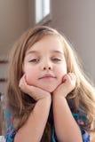 Den lilla gladlynta flickan lyfter tummen uppåt, på gräsplan Royaltyfri Fotografi