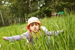 Den lilla gladlynta flickan som spelar i gräset, visar en nivå royaltyfri foto
