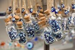 Den lilla glasflaskan som fylls med det blåa onda ögat, pryder med pärlor Arkivfoto