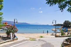 Den lilla grekiska byhamnen på en Amoulani ö, det heliga berget Athos är i bakgrund Royaltyfri Foto