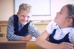 Den lilla grundskolastudentpojken försöker att störa flickan under kursen Pojkeförsök att nå baksidan för flicka` s Fotografering för Bildbyråer