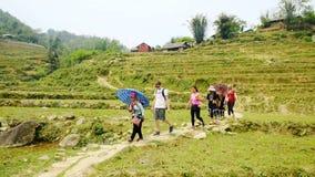 Den lilla gruppen av turister följer lokalt turnerar från svarta Hmong lager videofilmer