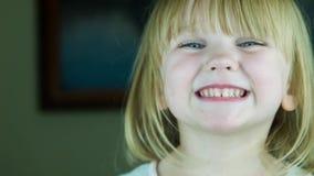 Den lilla gulliga flickan överför enkyss till kameran arkivfilmer