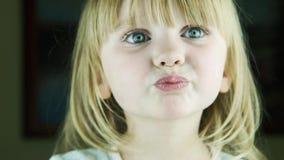 Den lilla gulliga flickan överför enkyss till kameran stock video