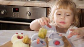 Den lilla gulliga flickan dekorerar den lilla kakan med hallonet arkivfilmer