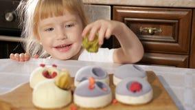 Den lilla gulliga flickan dekorerar den lilla kakan med hallonet lager videofilmer