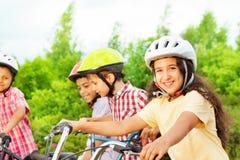 Den lilla gulliga flickan i hjälmhåll cyklar styret Arkivbild