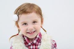 Den lilla gulliga flickan i pälsväst ler och ser upp Royaltyfri Bild