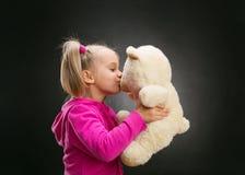 Den lilla gulliga flickan kysser leksakbjörnen Royaltyfri Fotografi