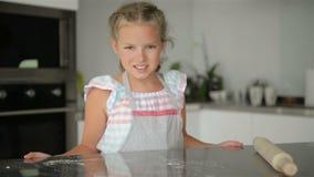 Den lilla gulliga flickan lagar mat p? k?k Ha gyckel, medan g?ra kakor och kakor Le och se kameran arkivfilmer