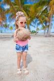 Den lilla gulliga flickan med en stor kokosnöt gömma i handflatan in dungen Arkivbilder