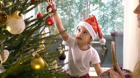 Den lilla gulliga flickan med hennes mamma dekorerar julgranen stock video