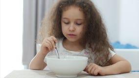 Den lilla gulliga flickan med lockigt h?r sitter p? en tabell och ?ter hans egen havremj?l, barnet ?ter g?rna Lyckligt begrepp lager videofilmer