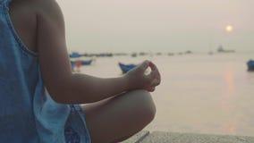 Den lilla gulliga flickan mediterar i turk poserar på sjösidan lager videofilmer