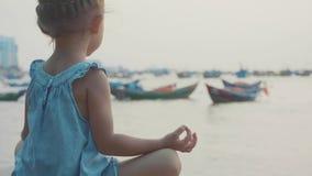 Den lilla gulliga flickan mediterar i turk poserar på sjösidan arkivfilmer
