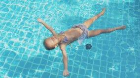 Den lilla gulliga flickan simmar på henne tillbaka i pölen i ultrarapid lager videofilmer