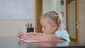 Den lilla gulliga flickan sitter i klassrum och handstil i skrivbok stock video