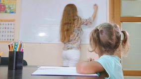Den lilla gulliga flickan sitter i klassrum och studier med läraren i skrivbok stock video