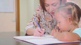 Den lilla gulliga flickan sitter i klassrum och studier med läraren i skrivbok lager videofilmer