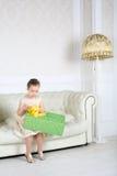 Den lilla gulliga flickan sitter på den vita soffan med den stora asken med gåvan Royaltyfri Fotografi