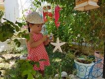 Den lilla gulliga flickan spelar med trädgårds- leksaker i kuriositet Arkivfoto