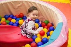 Den lilla gulliga leendeflickan spelar i bollar för en torr pöl Lekrum Lycka arkivfoton