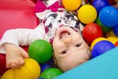 Den lilla gulliga leendeflickan spelar i bollar för en torr pöl Lekrum Lycka royaltyfri bild