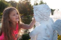 Den lilla gulliga lilla flickan förvånas av skulpturen i parkera arkivbilder