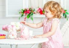 Den lilla gulliga lockiga flickan i en rosa klänning med snör åt och prickar som sitter på tabellen och äter olika sötsaker Arkivfoto