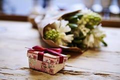 Den lilla gulliga närvarande asken med pilbågen på trätabellen, steg blommor bakom Begrepp för dag för St-valentin` s Arkivfoto