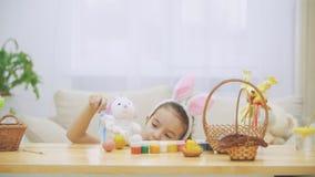 Den lilla gulliga och förtjusande flickan är le och spela med färgrika hönas ägg och kaniner Kaninen äter dess gunstling arkivfilmer