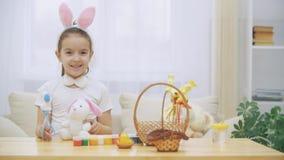 Den lilla gulliga och förtjusande flickan är le och spela med påskkaniner i hennes händer Begreppspåskferie stock video