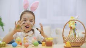 Den lilla gulliga och förtjusande flickan ler uppriktigt Hon tar ett påskägg och visar resultatet av hennes arbete, genom att anv stock video