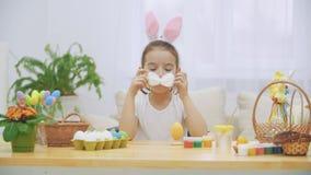 Den lilla gulliga och förtjusande flickan ler uppriktigt Flickan spelar med en fluffig fluga på hennes hals Flickan klär arkivfilmer