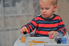 Den lilla gulliga pojken drar målarfärger och fingrar royaltyfri foto