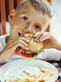 Den lilla gulliga pojken 6 gamla år med hamburgaren och fransman steker framställning av galna framsidor Arkivbild