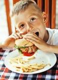 Den lilla gulliga pojken 6 gamla år med hamburgaren och fransman steker maki royaltyfria bilder